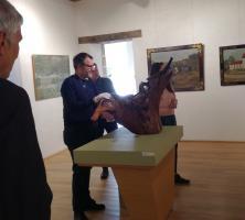 Toucher d'une sculpture sur bois par les visiteurs